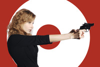 Businesswoman aiming a pistol