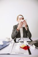 Businesswoman blowing her nose with tissue