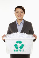Businesswoman carrying a box filled with shredded paper