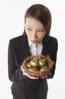 Businesswoman carrying a nest filled with gold eggs