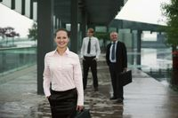 Businesswoman carrying bag, businessmen in the background