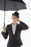 Businesswoman covering her eyes while standing under the umbrella