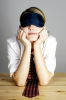 Businesswoman covering her eyes with an eye mask