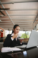 Businesswoman drinking coffee while using laptop
