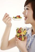 Businesswoman eating a spoonful of mixed fruits
