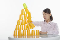 Businesswoman hitting pyramid of disposable cups