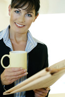 Businesswoman holding newspaper and a cup of coffee