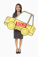 Businesswoman holding up a cardboard car with a sold