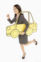 Businesswoman holding up a cardboard car