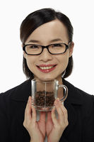 Businesswoman holding up a cup of coffee beans