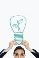 Businesswoman holding up a cut out light bulb