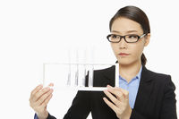 Businesswoman holding up a tray of test tubes