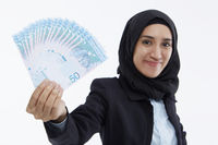 Businesswoman holding up cash