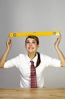 Businesswoman placing a spirit level on her head