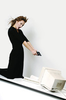 Businesswoman pointing her pistol at a computer monitor