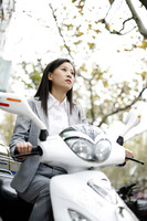 Businesswoman riding on a scooter