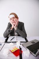 Businesswoman sitting at the table, having cold and flu