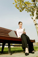 Businesswoman sitting on the bench text messaging and using laptop