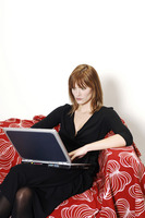 Businesswoman sitting on the couch using laptop