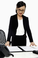Businesswoman standing and looking at her notes