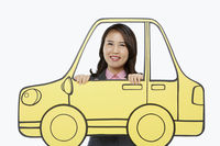 Businesswoman standing behind a cardboard car