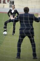 Businesswoman standing on football with businessman as the goal keeper