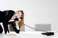Businesswoman struggling to answer a phone call