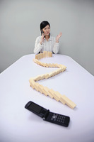 Businesswoman talking on mobile phone with wooden blocks on the table