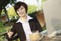 Businesswoman text messaging and smiling