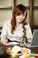 Businesswoman using laptop and writing information into organizer