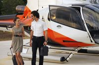 Businesswoman walking away from helicopter with pilot