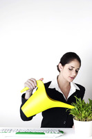Businesswoman watering the plants