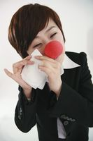 Businesswoman wearing a clown's nose wiping tears with tissue