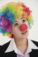 Businesswoman wearing a clown's wig and nose looking up