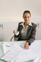 Businesswoman with a cup of coffee, blueprints on the table