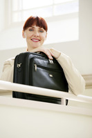 Businesswoman with a laptop bag looking at the camera