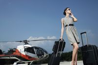 Businesswoman with luggages and briefcase talking on the phone at helipad