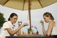 Businesswomen playing chess by the poolside