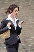 Busy business woman text messaging while walking to work