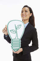 Cheerful businesswoman holding up a cut out light bulb