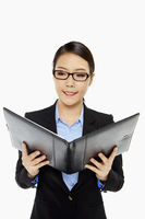 Cheerful businesswoman reading notes from a folder