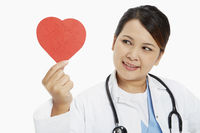 Cheerful medical personnel holding up a red heart