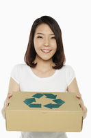 Cheerful woman carrying a recyclable cardboard box