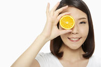 Cheerful woman covering her eye with an orange