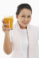 Cheerful woman holding up a glass of orange juice