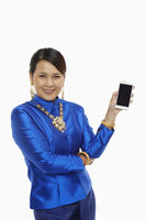 Cheerful woman in traditional clothing holding up a mobile phone