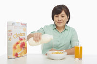 Cheerful woman pouring milk into a bowl of cereals