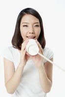 Cheerful woman talking into a paper cup phone