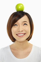 Cheerful woman with an apple on her head