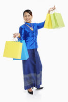 Cheerful women in traditional clothing carrying paper bags